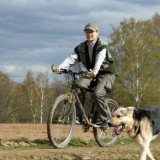 Woman at bicycle with alsatian dog